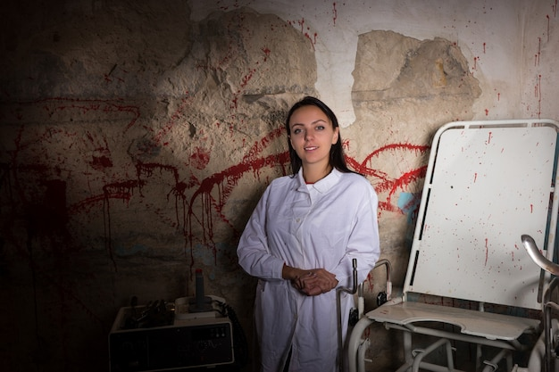 Smiling woman scientist in front of a blood splattered wall, halloween concept