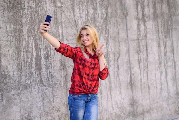 笑顔の女性の自画像携帯電話の勝利のサイン