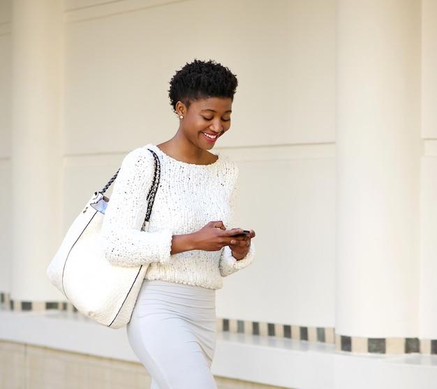 휴대 전화에 문자 메시지를 보내는 웃는 여자