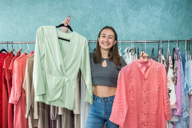Smiling woman shopper choosing new garments at fashion story. lifestyle
