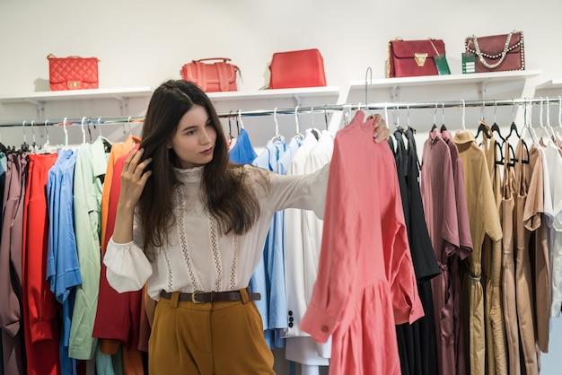 Smiling woman shopper choosing new garments at fashion story
