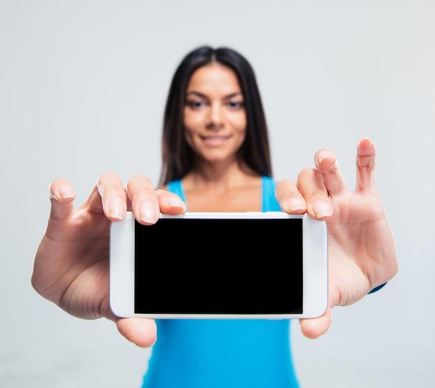 空白のスマートフォン画面を表示している笑顔の女性