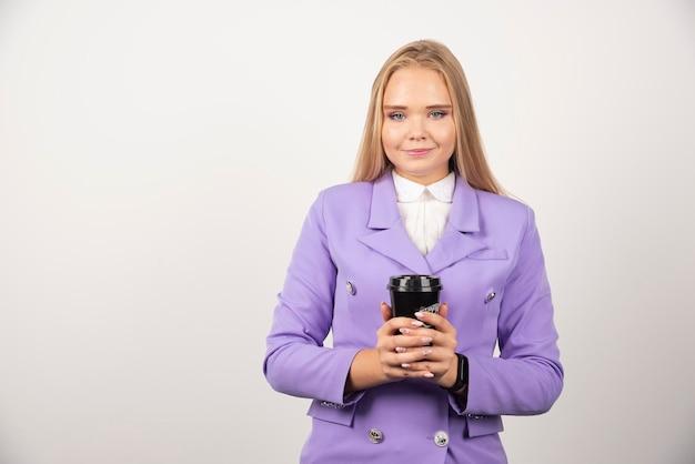 白い背景の上のコーヒーのカップを示す笑顔の女性。高品質の写真