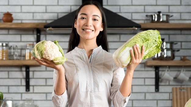 Smiling woman showing fresh green cauliflower and lettuce in kitchen