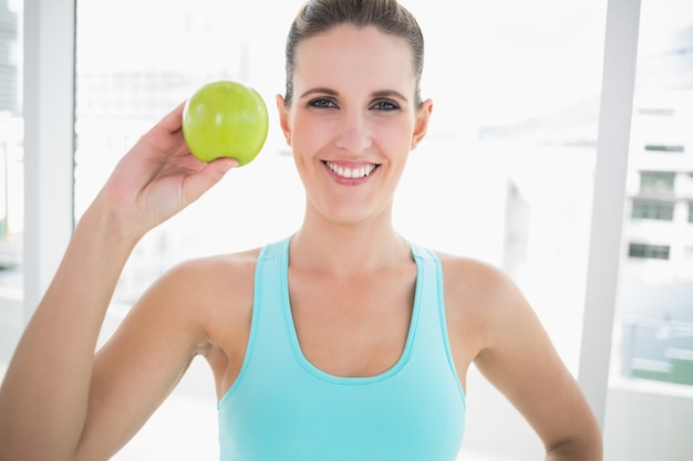 Smiling woman showing green apple