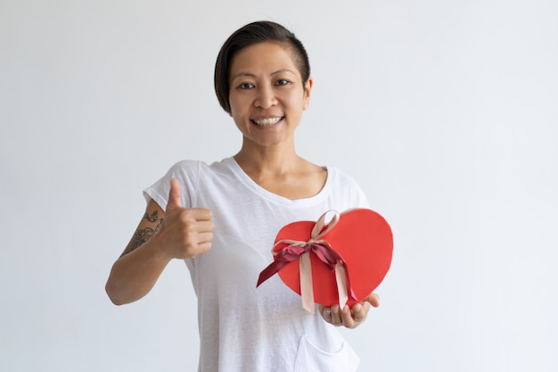 Smiling woman showing heart shaped gift box and thumb up