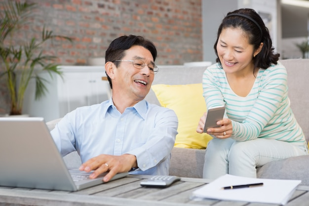 Smiling woman showing smartphone to her husband in the living room