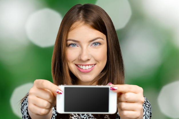 Smiling woman showing smartphone screen