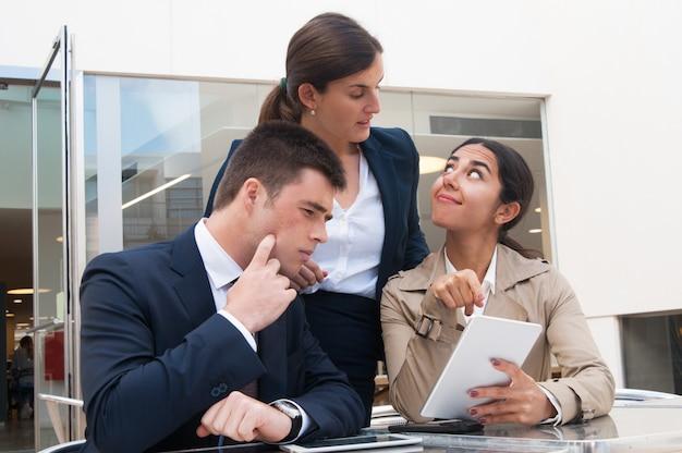 ビジネスの方々に笑顔の女性示すタブレット画面