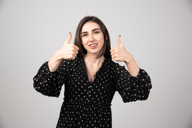 Smiling woman showing thumbs up and looking at the camera over gray background.