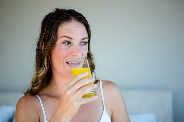 Smiling woman sipping a glass of orange juice in her bedroom