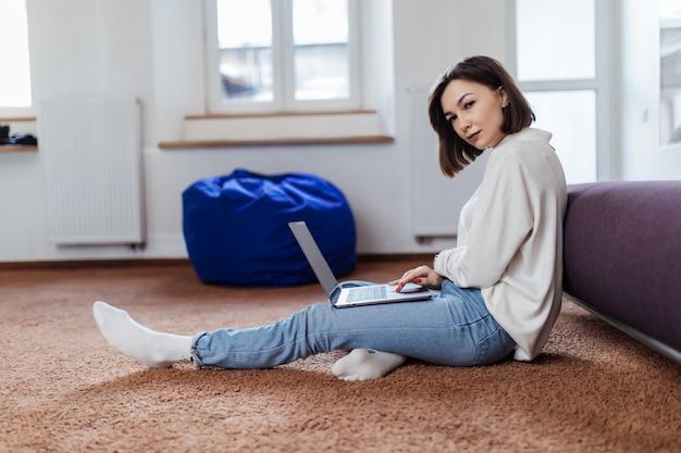 Улыбающаяся женщина сидит на полу со своим новым ноутбуком и смотрит видео