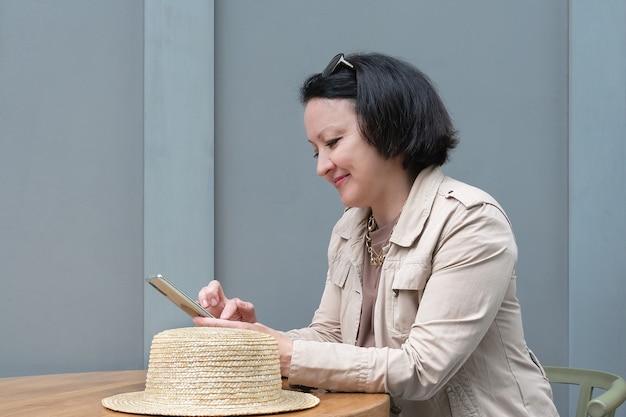 笑顔の女性がカフェのテーブルに座って電話でメッセージを書いています。