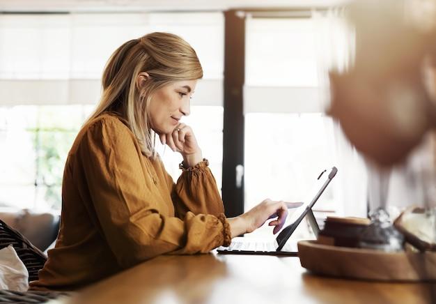 タブレット コンピューターの前のキッチン テーブルに座って、ホーム オフィスで仕事をする笑顔の女性