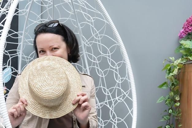 笑顔の女性がカフェのサマーテラスの肘掛け椅子に座り、麦わら帽子で顔を覆っている。