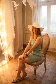 Улыбающаяся женщина сидит на изящном стуле и любуется своим отражением