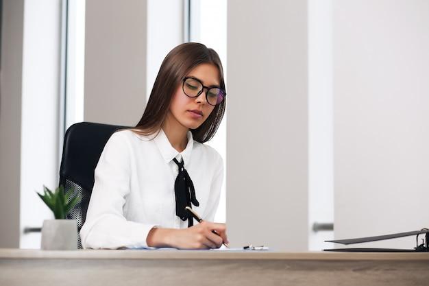 사무실에서 그녀의 책상에 앉아 웃는 여자. 사무실에 앉아 행복 한 비즈니스 우먼