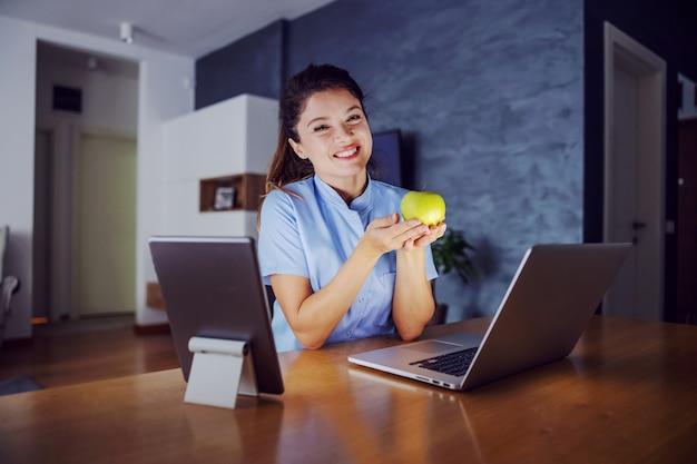 ノートパソコンとタブレットに囲まれて家に座り、リンゴを手に持つ笑顔の女性