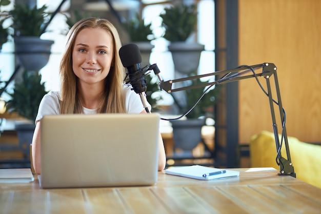 Улыбающаяся женщина, сидящая за столом и работающая в ноутбуке
