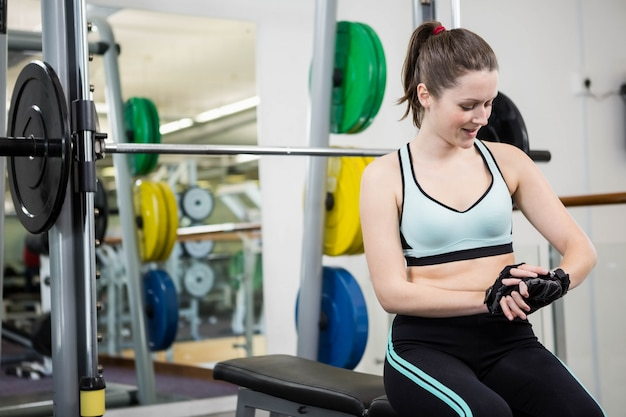 Smiling woman sitting on barbell bench in the gym