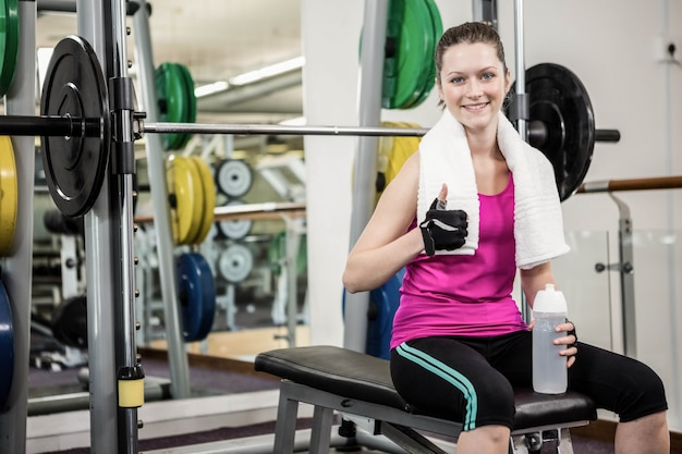 Smiling woman sitting on barbell bench and showing thumb up at the gym