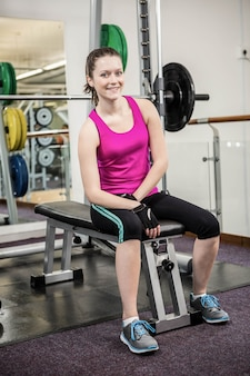 Smiling woman sitting on barbell bench