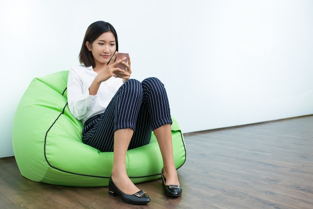 Smiling woman sitting on beanbag reading message