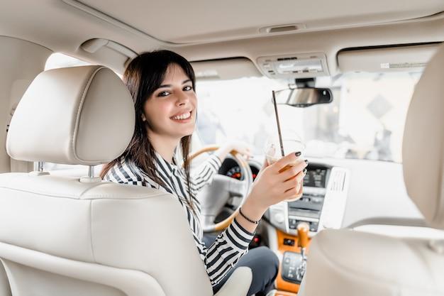 アイスコーヒーを飲む車のホイールの後ろに座っている笑顔の女性