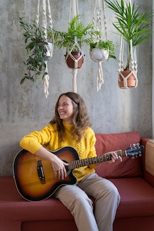 Smiling woman sitting on couch under cotton macrame plant hanger with houseplants, plays the guitar