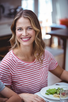 Smiling woman sitting at dining table