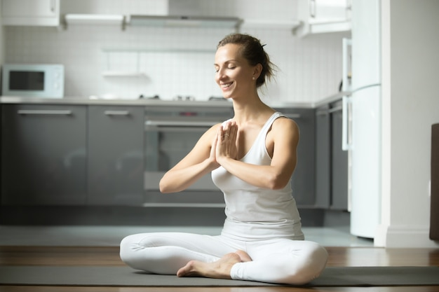 Smiling woman sitting in half lotus exercise