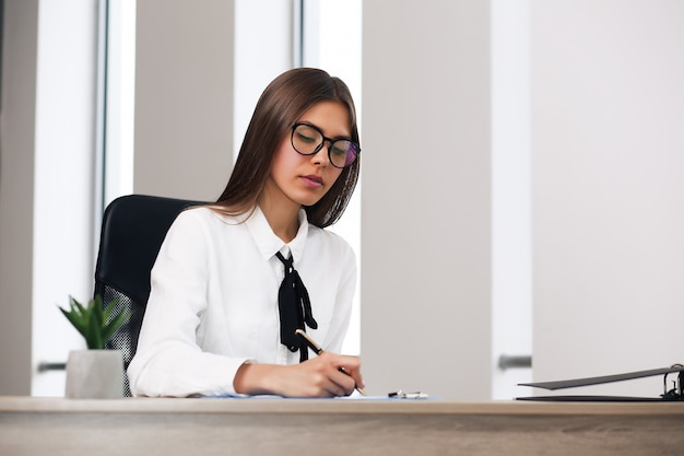Smiling woman sitting at her desk in the office. happy business woman sitting in the office