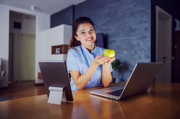 Smiling woman sitting at home surrounded by laptop and tablet and holding apple in hands