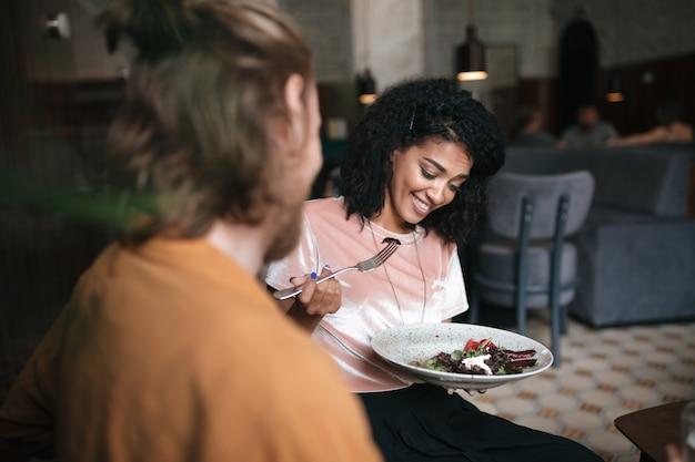 친구와 함께 레스토랑에 앉아 웃는 여자