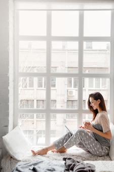 Smiling woman sitting near white window and chatting on laptop.