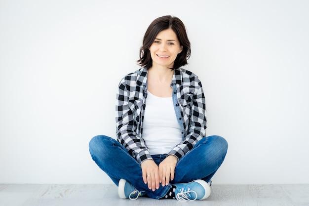 白い壁の背景に床に座っている笑顔の女性