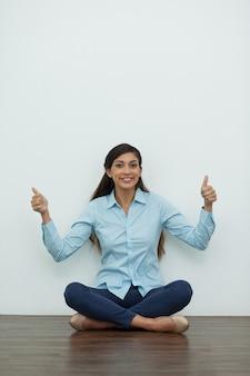 Улыбается женщина сидит на полу с большими пальцами вверх