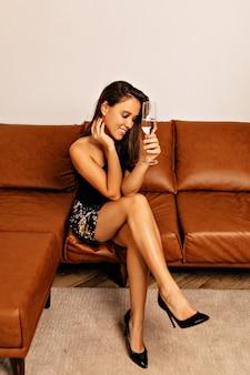Улыбающаяся женщина, сидящая на диване с ярким макияжем и волнистыми волосами с бокалом вина