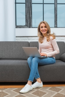 Smiling woman sitting on sofa with laptop on her lap looking at camera
