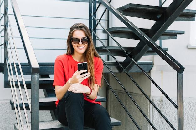 携帯電話を使って階段に座っている笑顔の女性