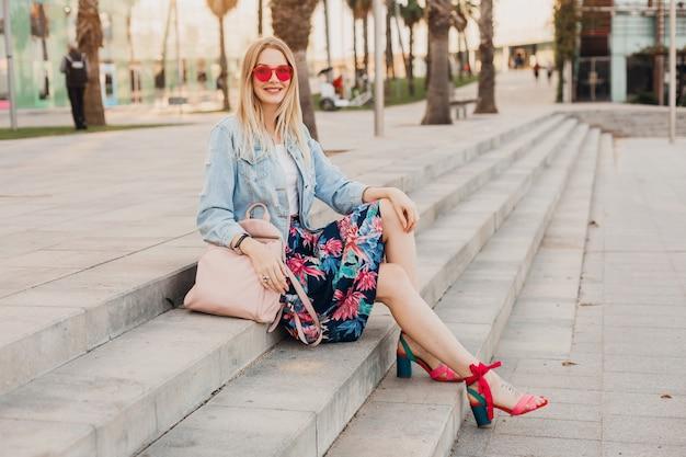 ピンクのサングラスをかけている革のバックパックとスタイリッシュなプリントスカートとデニムの特大ジャケットの街の階段に座っている女性の笑みを浮かべてください。