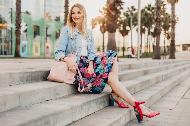 革のバックパックとスタイリッシュなプリントスカートとデニムの特大ジャケットで街の階段に座っている女性の笑みを浮かべてください。