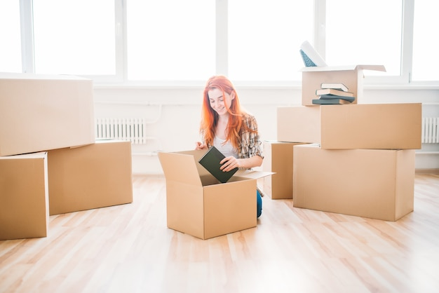 段ボール箱の間の床に座って、新築祝いの笑顔の女性。新しい家への移転