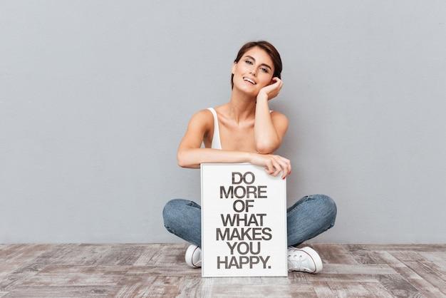 Улыбающаяся женщина сидит на полу и держит доску с мотивационной фразой, изолированной на сером фоне