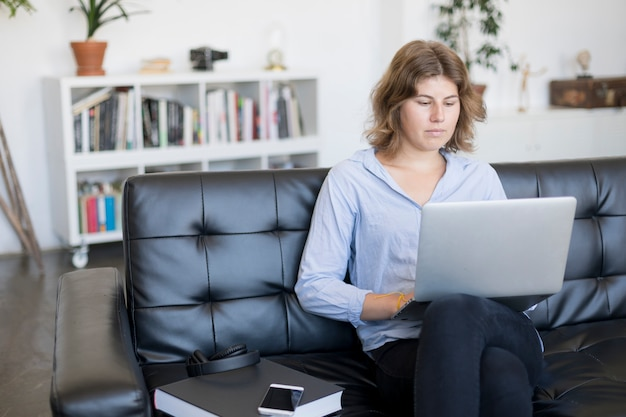 Smiling woman sitting on a sofa at home using a laptop