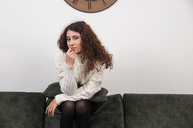 Una donna sorridente seduta sul divano e guardando la telecamera