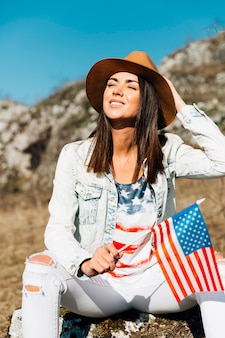 Smiling woman sitting on stone with flag