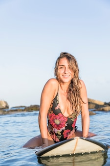 Smiling woman sitting on surfboard