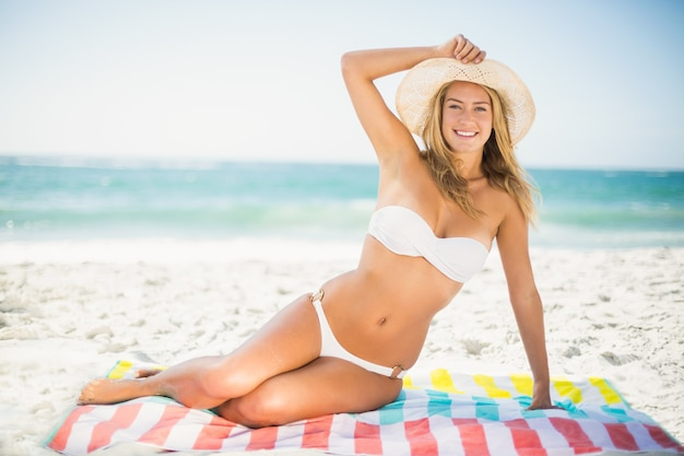 Smiling woman sitting on a towel at the beach