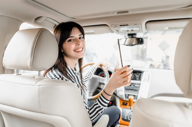 Smiling woman sitting behind a wheel of a car drinking iced coffee